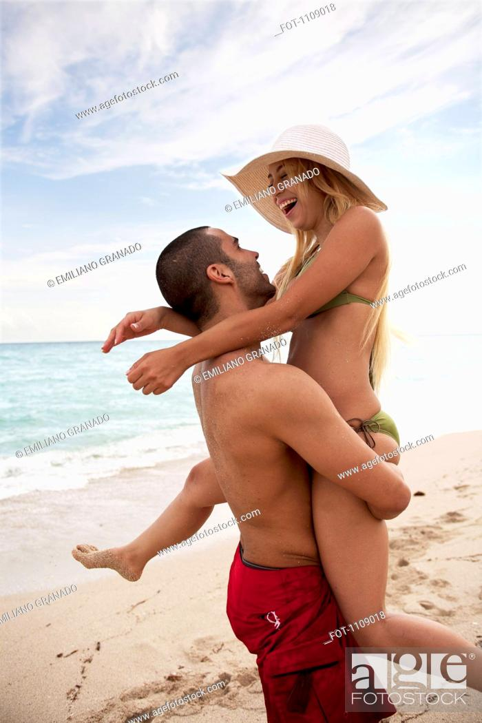 Stock Photo: A playful young couple at the beach.