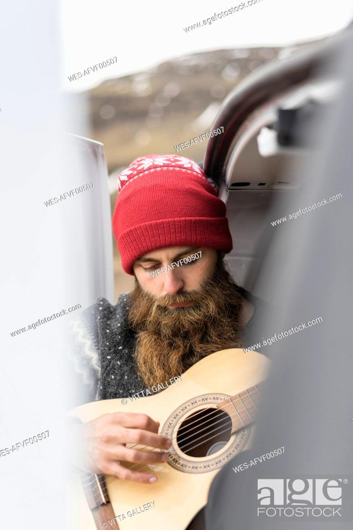 Stock Photo: Portrait of hipster wearing red woolly hat playing guitar.