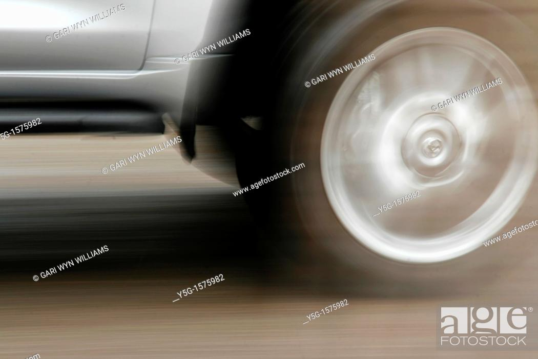 Stock Photo: fast car driving on street surface.