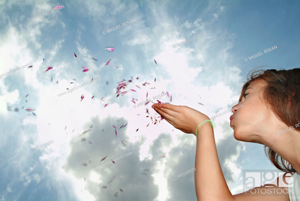 Stock Photo: Teenage Girls, blowing into the sky the little petals of a flower.