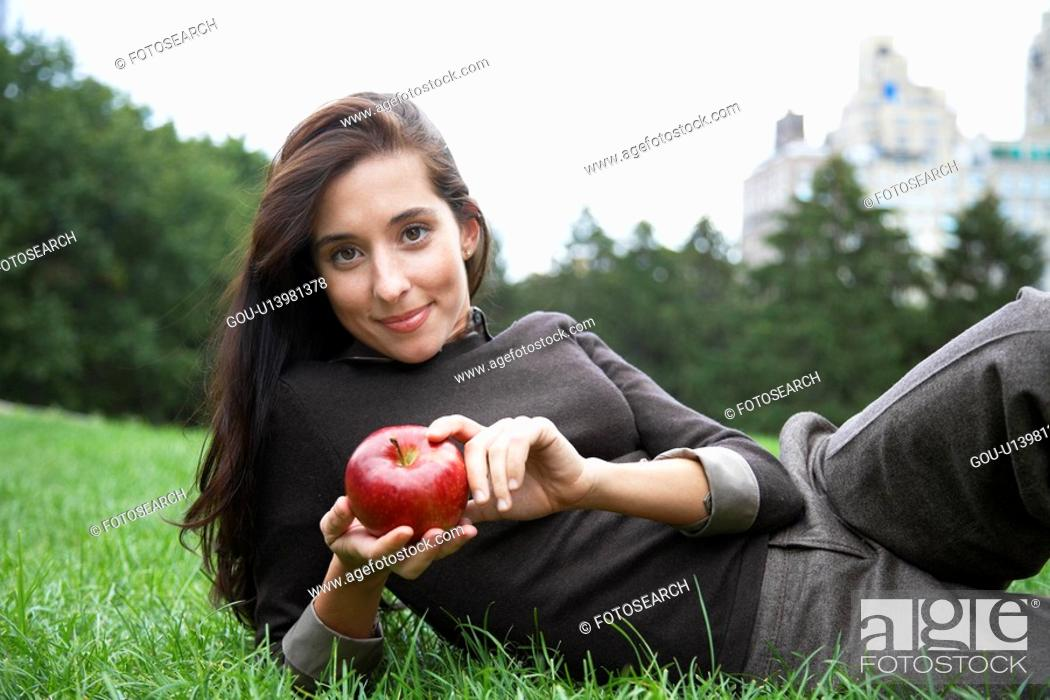 Stock Photo: Young woman eating apple on grass (portrait).