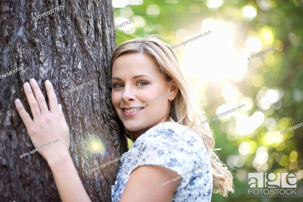 Stock Photo: Woman hugging tree outdoors.
