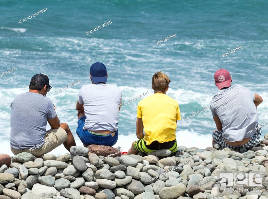 Stock Photo: Young men watching windsurfing competition at Pozo Izquierdo on Gran Canaria, Canary Islands, Spain, Europe.