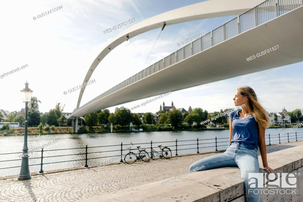 Stock Photo: Netherlands, Maastricht, young woman sitting on a wall at the riverside.