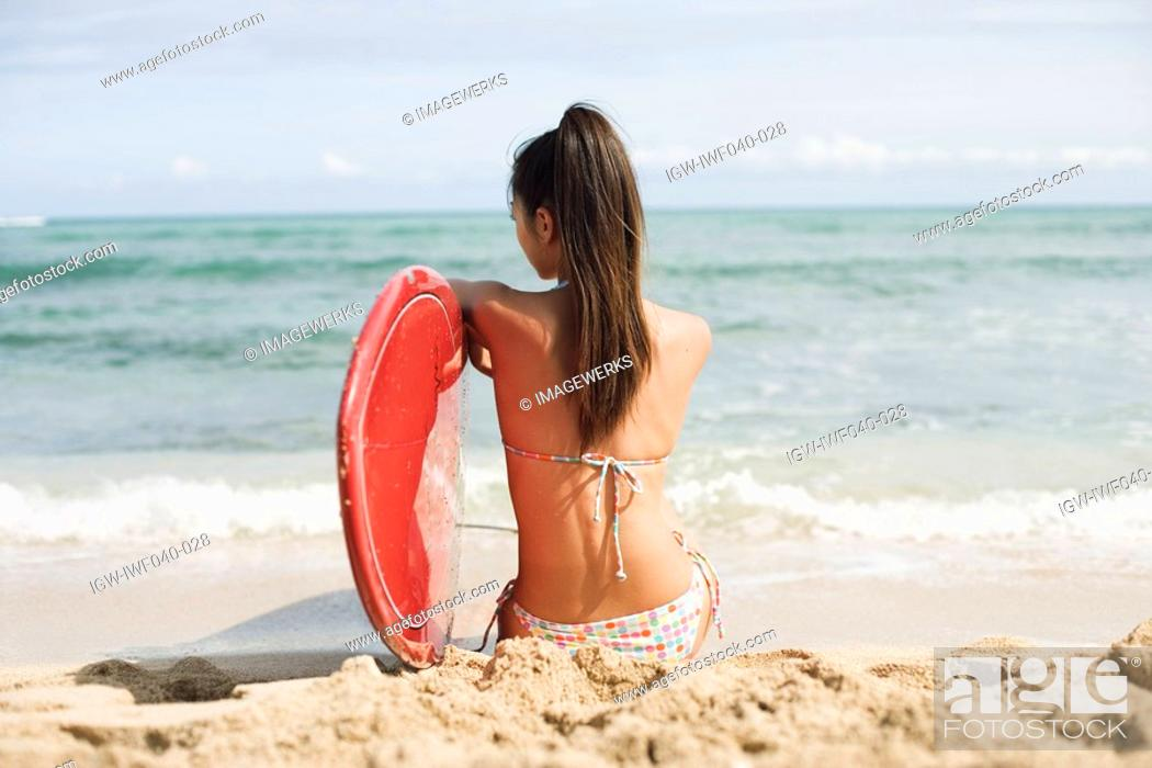 Stock Photo: Rear view of a young woman sitting on beach.