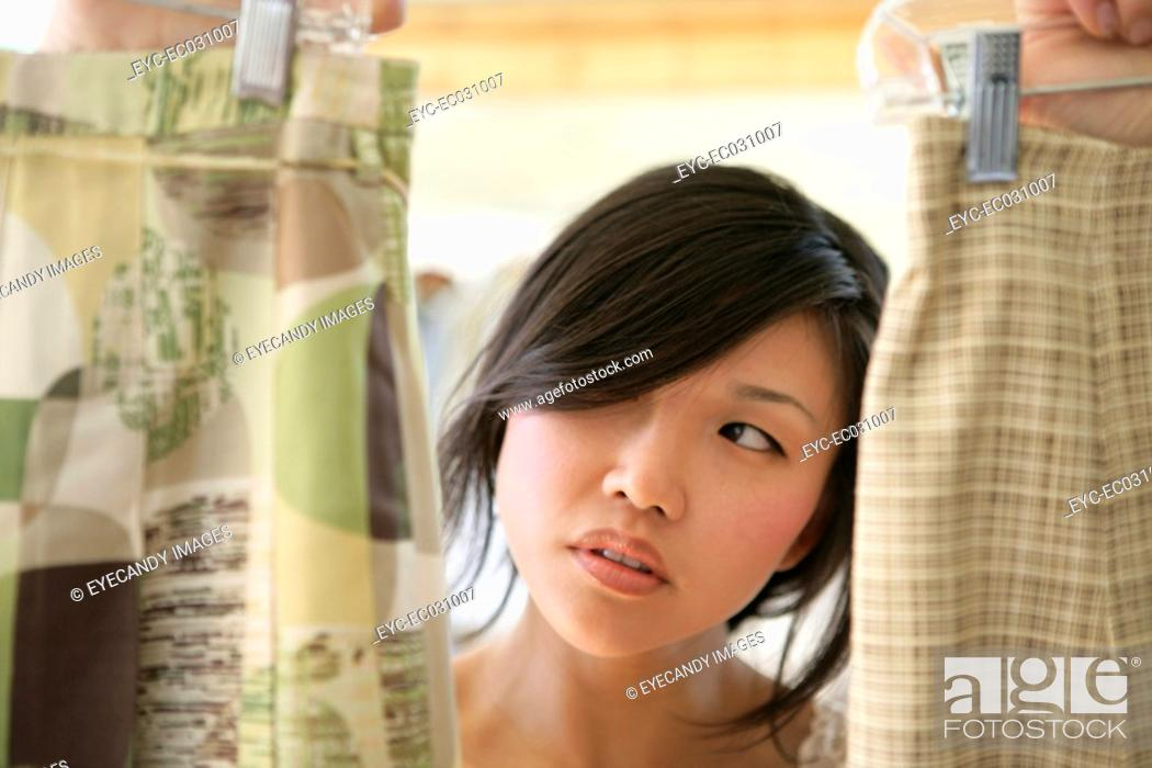 Stock Photo: Young woman choosing dress, close-up.