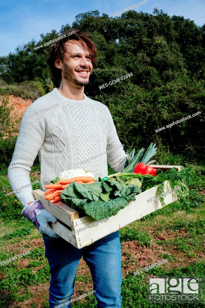 Stock Photo: Man carrying crate with freshly harvested vegetables from his vegetable garden.