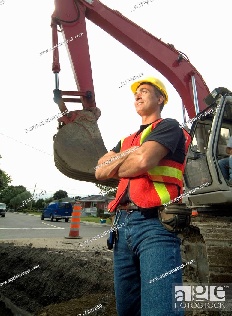 Stock Photo: Construction Worker Smiling with Arms Crossed in front of a Front Shovel Excavator, Montreal, Quebec.
