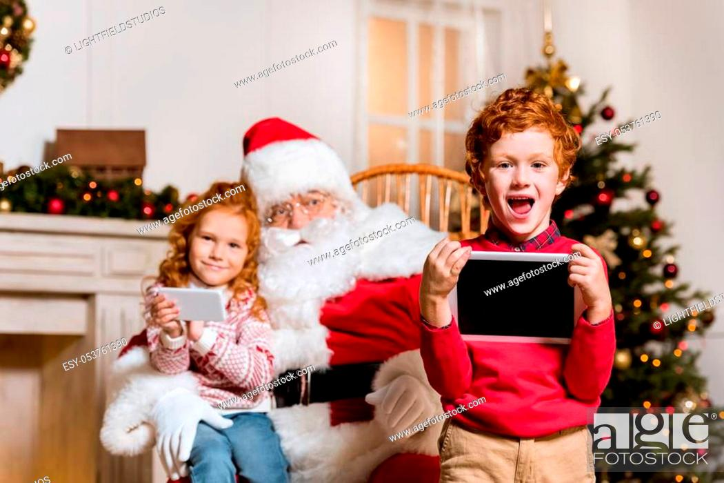 Stock Photo: portrait of santa claus in rolling chair and children with digital devices.
