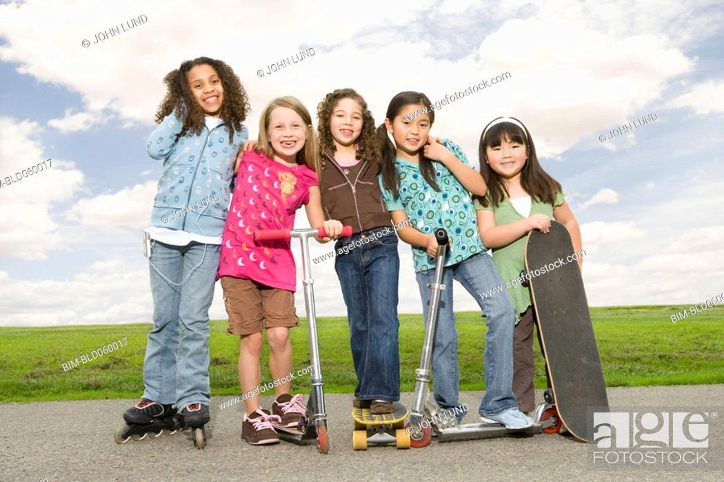 Stock Photo: Multi-ethnic girls on roller skates, scooters and skateboards.