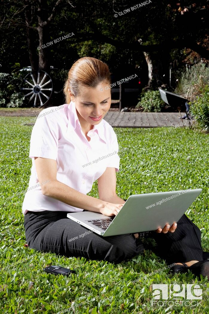 Stock Photo: Businesswoman using a laptop in a park.