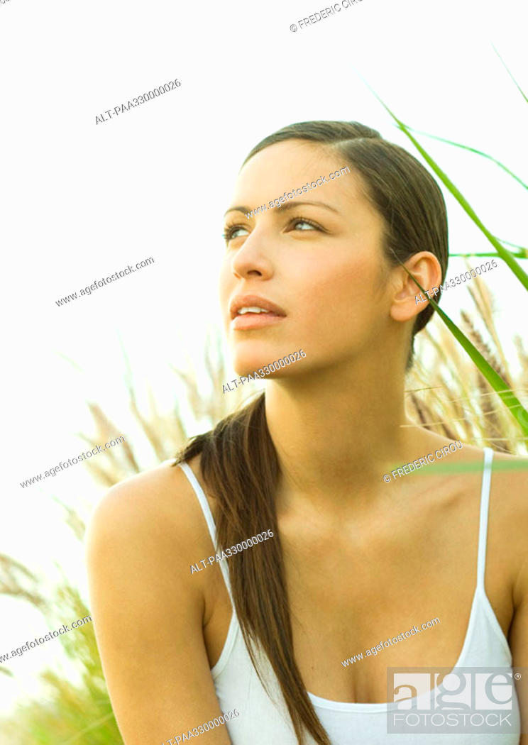 Stock Photo: Woman in long grass, looking up.
