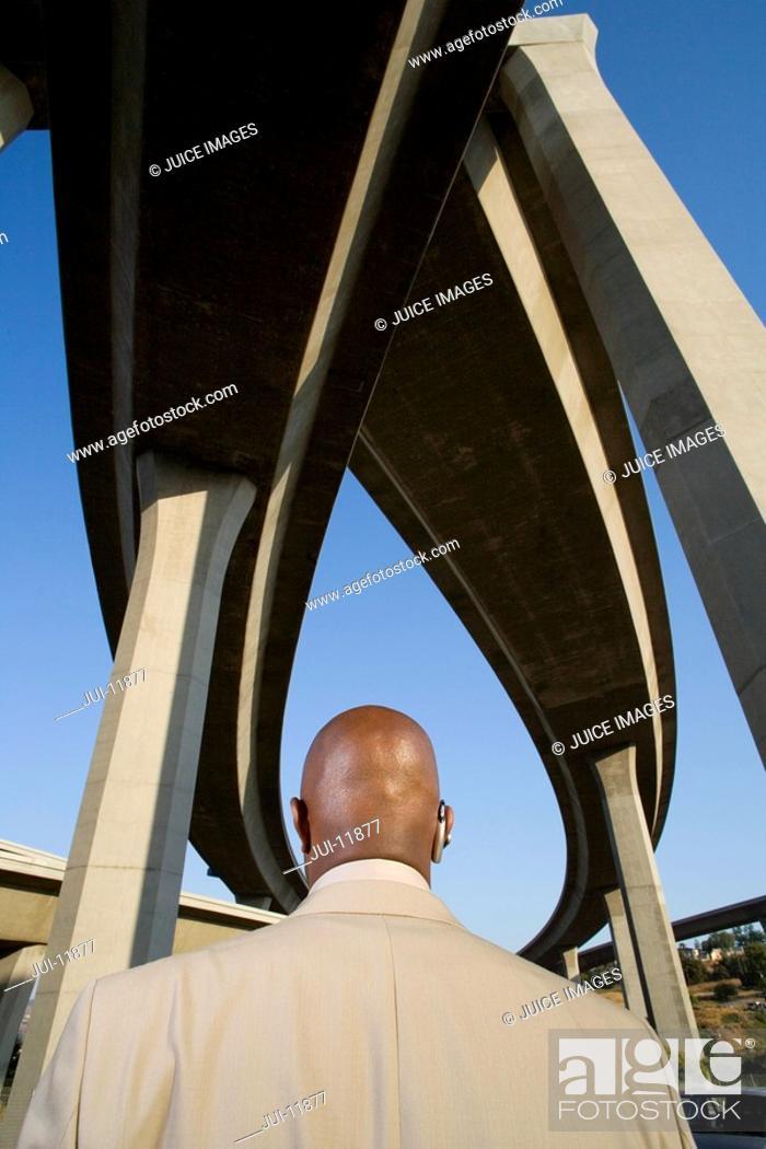 Stock Photo: Businessman beneath overpasses, rear view.