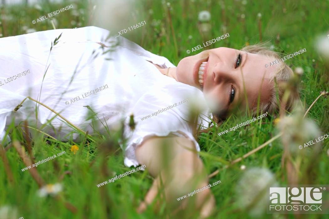 Stock Photo: Portrait of young blonde woman lying on meadow.