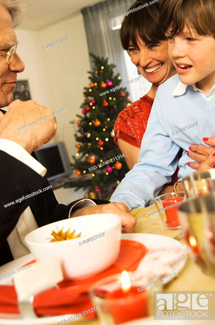 Stock Photo: Close-up of grandparents sitting with their grandson at a dining table.