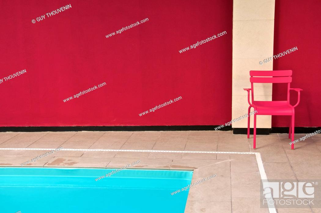 Imagen: Pink metal chair and blue water of indoor swimming pool Best Western Hotel Reims Marne 51 France.