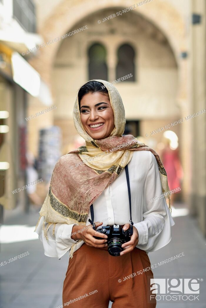 Stock Photo: Spain, Granada, young Arab tourist woman wearing hijab, using camera during sightseeing in the city.