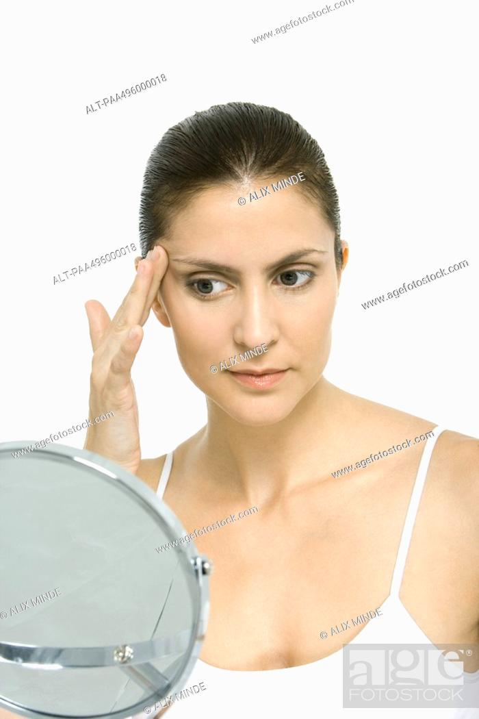 Stock Photo: Woman looking at self in mirror, touching temple.