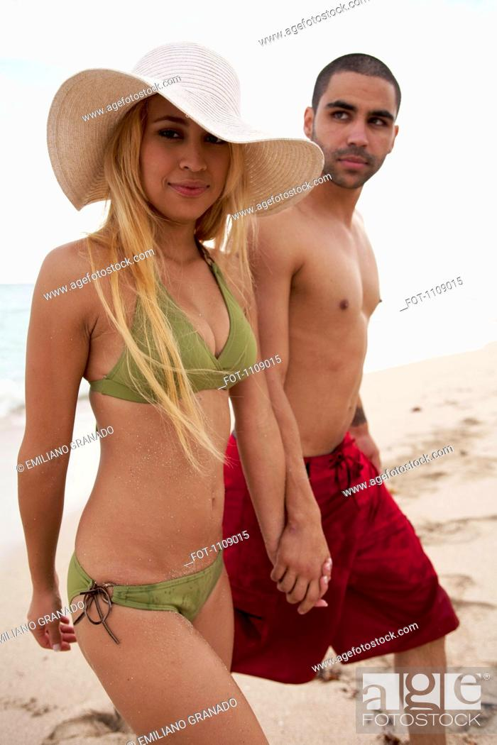 Stock Photo: A young couple holding hands and walking on the beach.