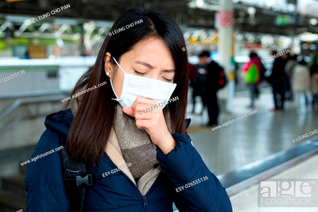 Stock Photo: Woman feeling unwell and wearing face mask in train station.