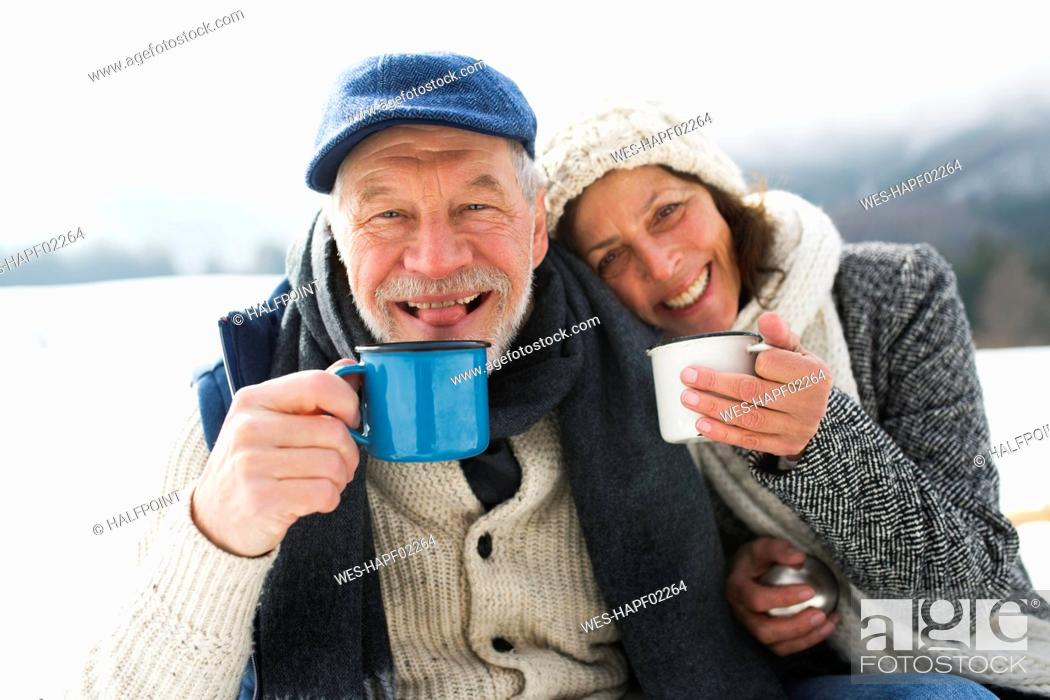 Stock Photo: Portrait of senior couple with hot beverages in winter.