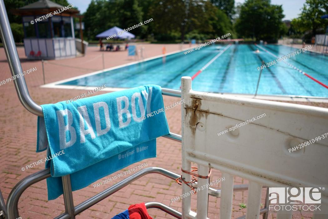 "Stock Photo: 10 June 2020, Berlin: A towel with the imprint """"Bad Boy"""" is lying on the railing of the diving tower in the summer pool Pankow."