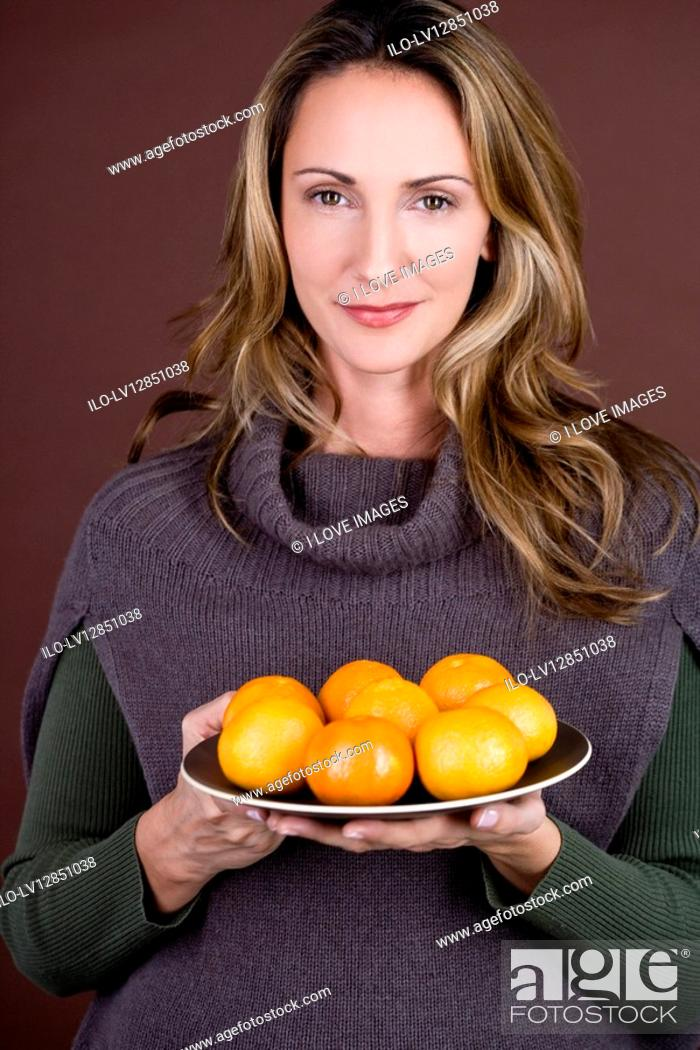 Stock Photo: A mid adult woman holding a plate of clementines.