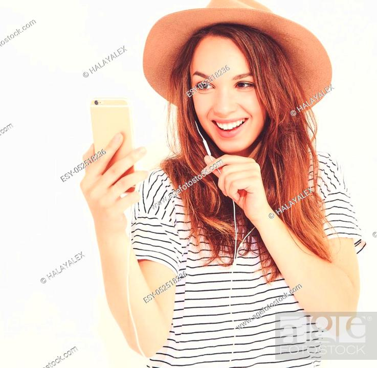 Stock Photo: beautiful smiling brunette woman girl in casual hipster summer clothes with no makeup in brown hat listening music in smartphone with headphones isolated on.