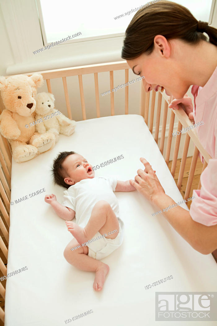 Stock Photo: Mother with baby in crib.