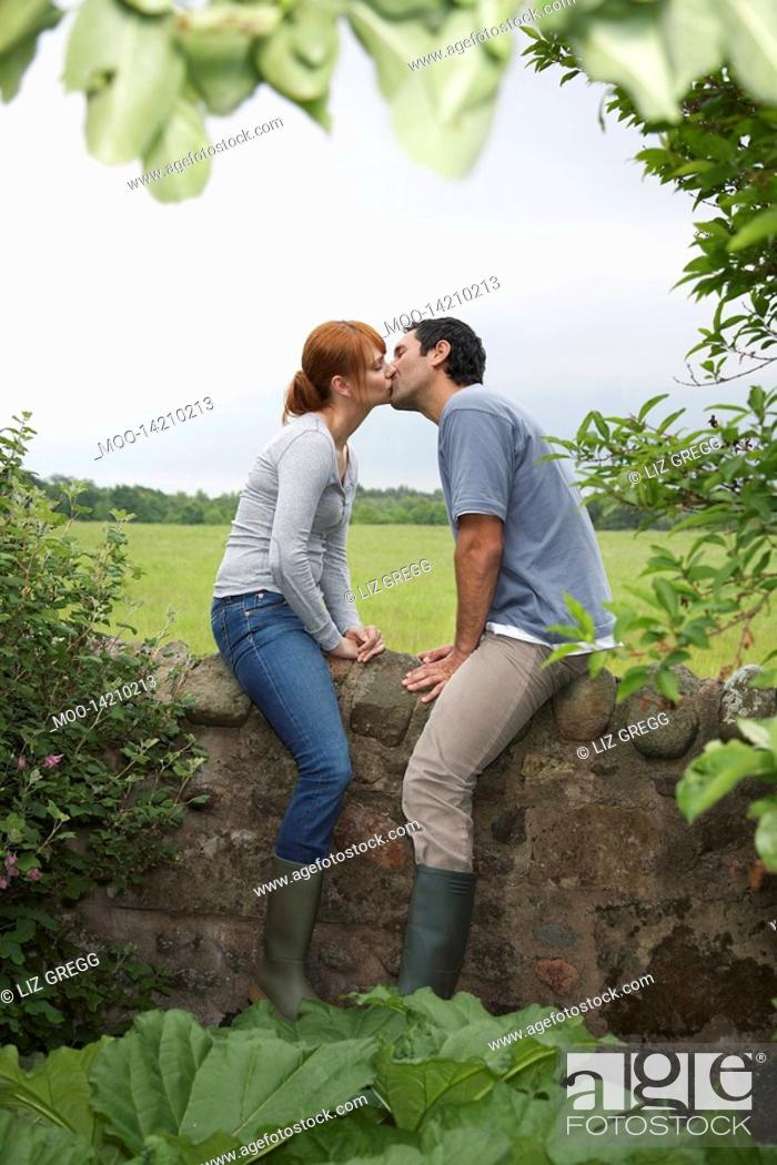 Stock Photo: Couple kissing on wall in countryside.
