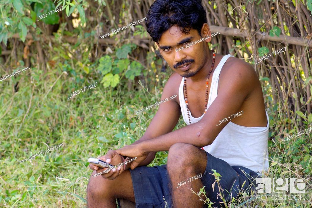 Stock Photo: an indian man using a cellphone, looking at camera  Elephanta island  mumbai  maharashtra  india.