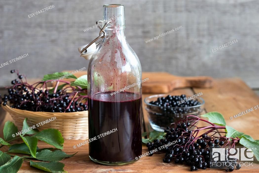Stock Photo: A bottle of homemade elderberry syrup on a wooden table, with fresh elderberries in the background.