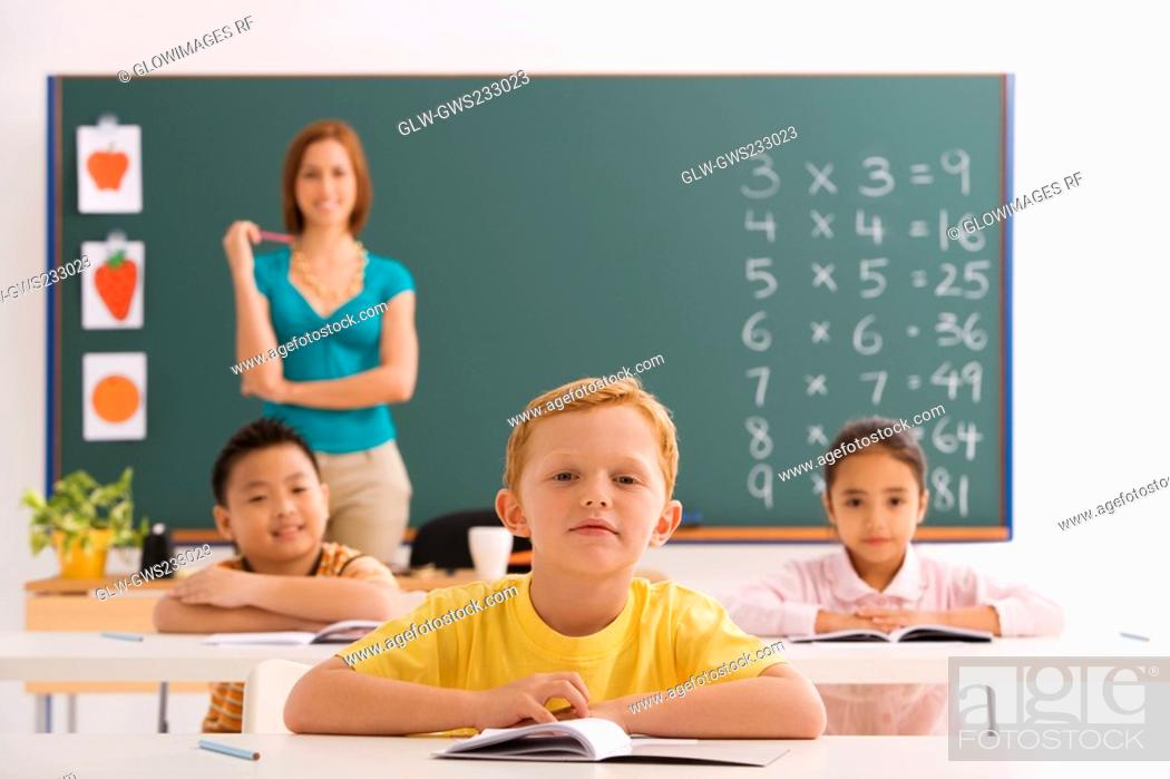 Stock Photo: Three students sitting in a classroom with their teacher standing in the background.