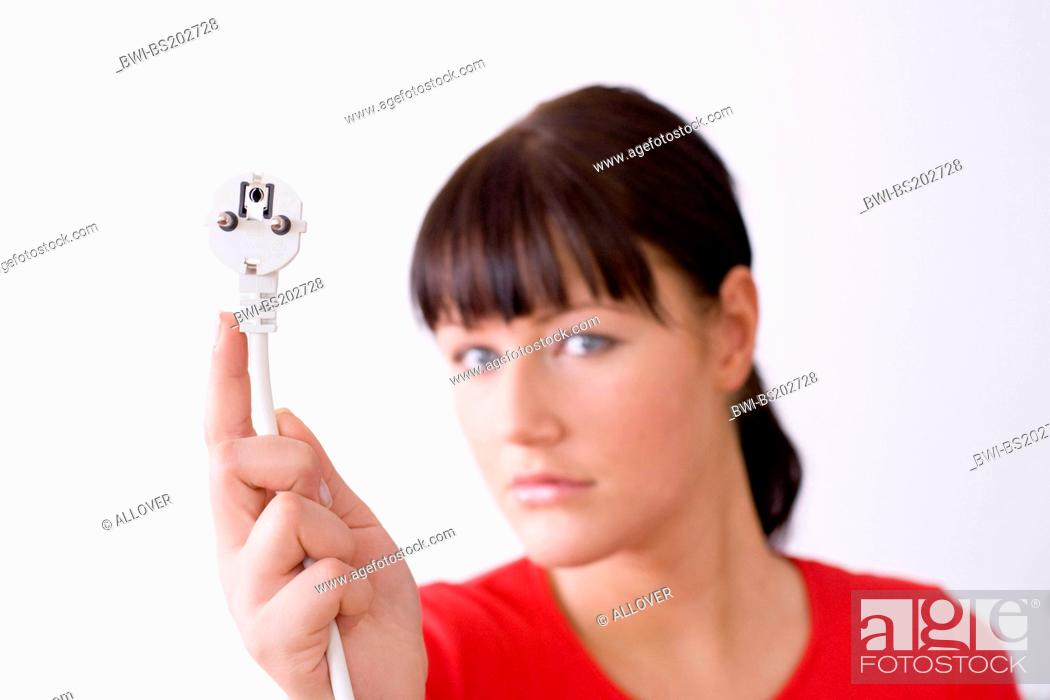 Stock Photo: portrait of a darkhaired young woman with a plug in her hand.