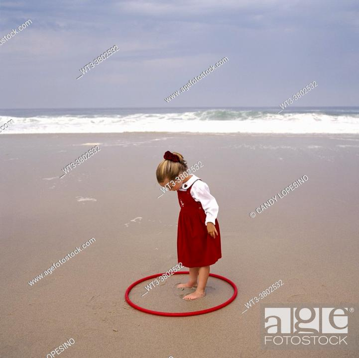 Stock Photo: Little three-year-old girl with a red hula hoop playing in the sand on the beach on a sunny day by the sea.