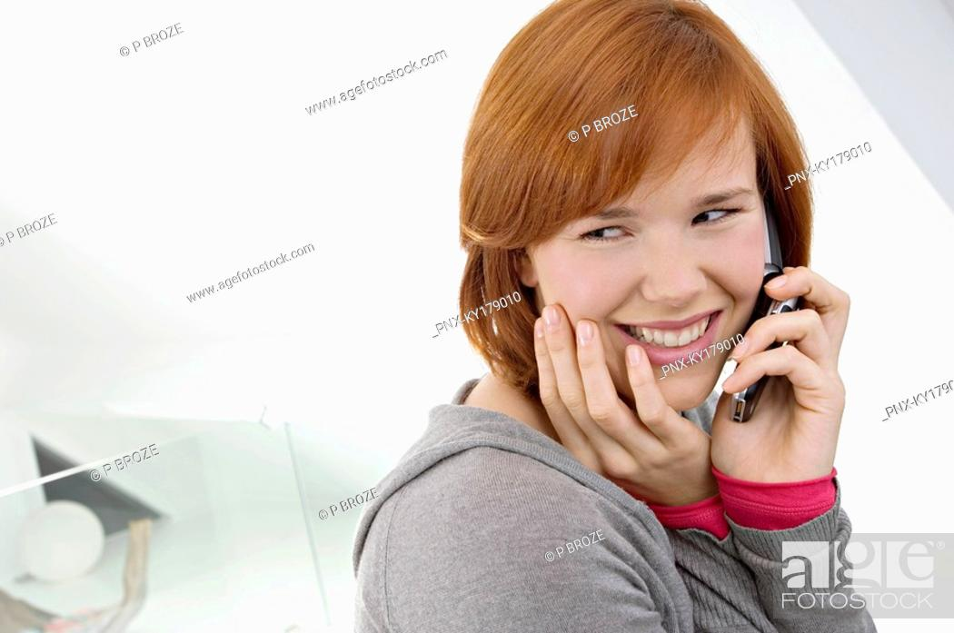 Stock Photo: Side profile of a young woman using a mobile phone and smiling.
