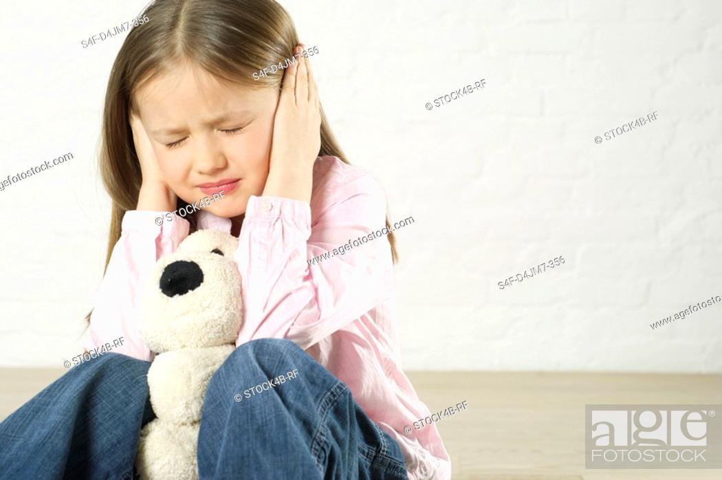 Stock Photo: Girl covering ears with hands.