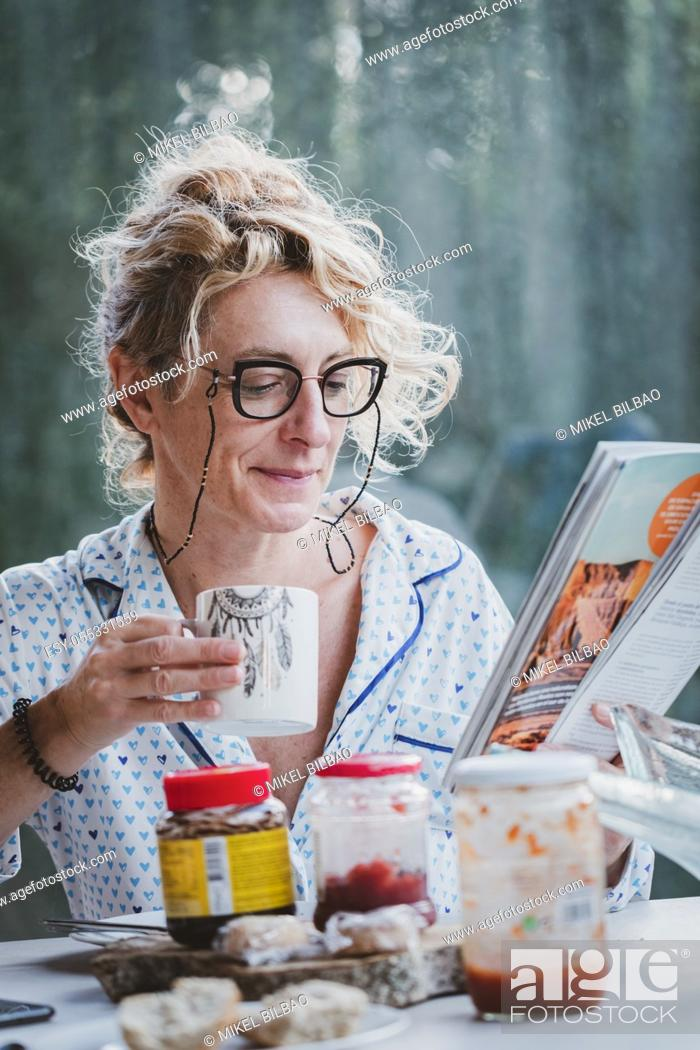 Stock Photo: Blonde young mature woman with glasses in pyjamas at home in breakfast time, reading a magazine and having a cup of coffee.