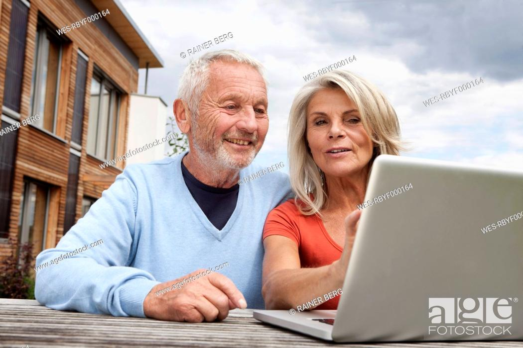 Stock Photo: Germany, Bavaria, Nuremberg, Senior couple using laptop.