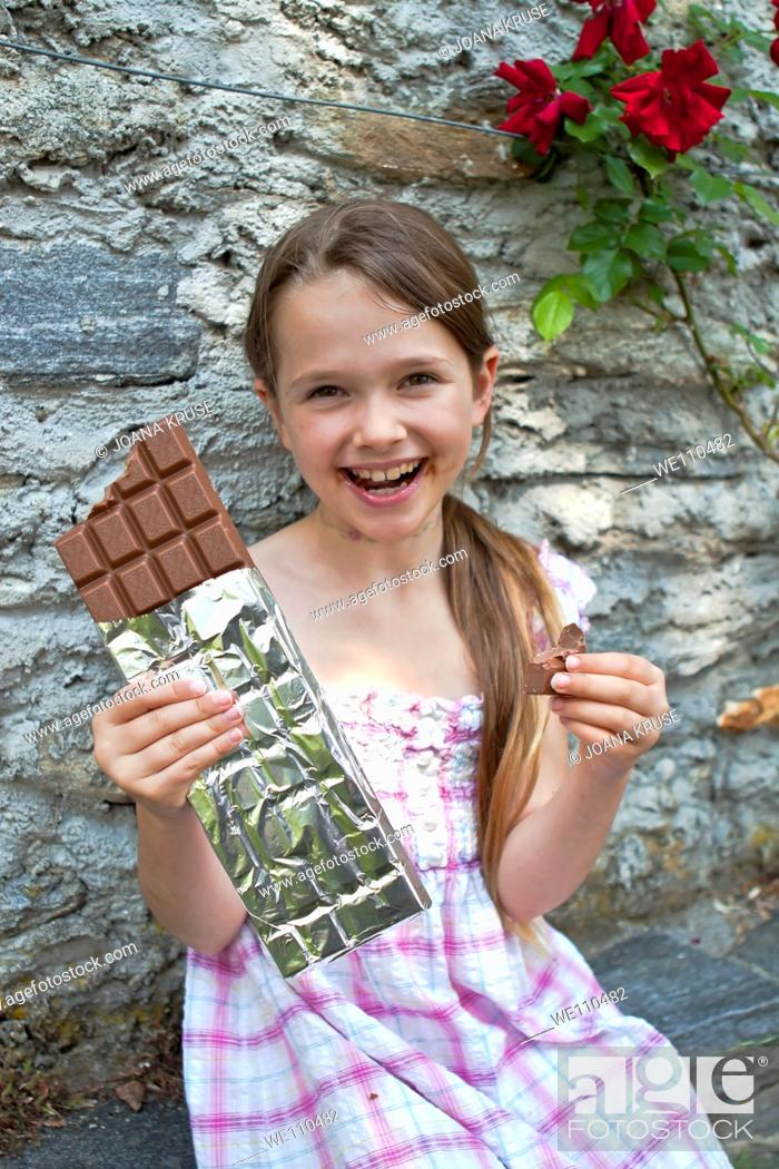 Stock Photo: seven year old girl eats chocolate.