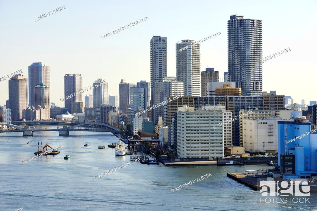 Stock Photo: Aerial view of Tokyo Bay. The high rise buildings are located in Chuo Ward. The body of water is that Sumida River and it flow trough the Kachidoki bridge.