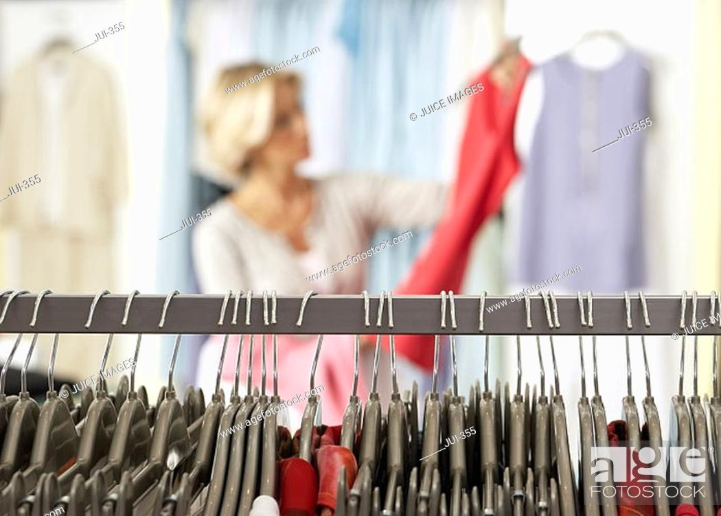 Stock Photo: Mature woman shopping in clothes shop, holding red top, focus on clothes rail in foreground.