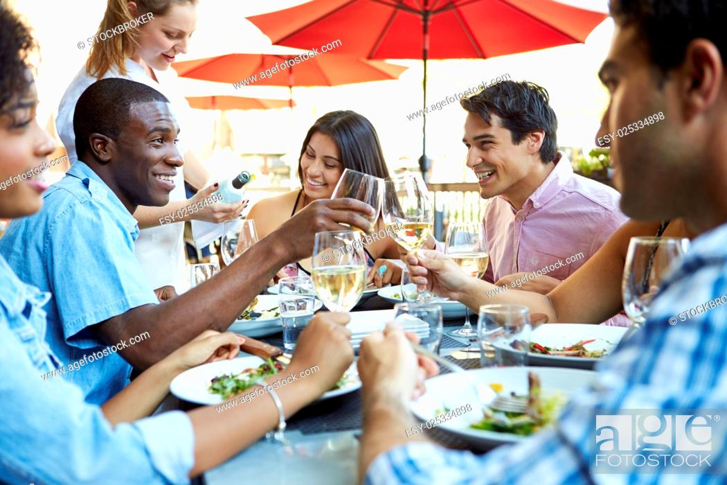 Stock Photo: Group Of Friends Enjoying Meal At Outdoor Restaurant.