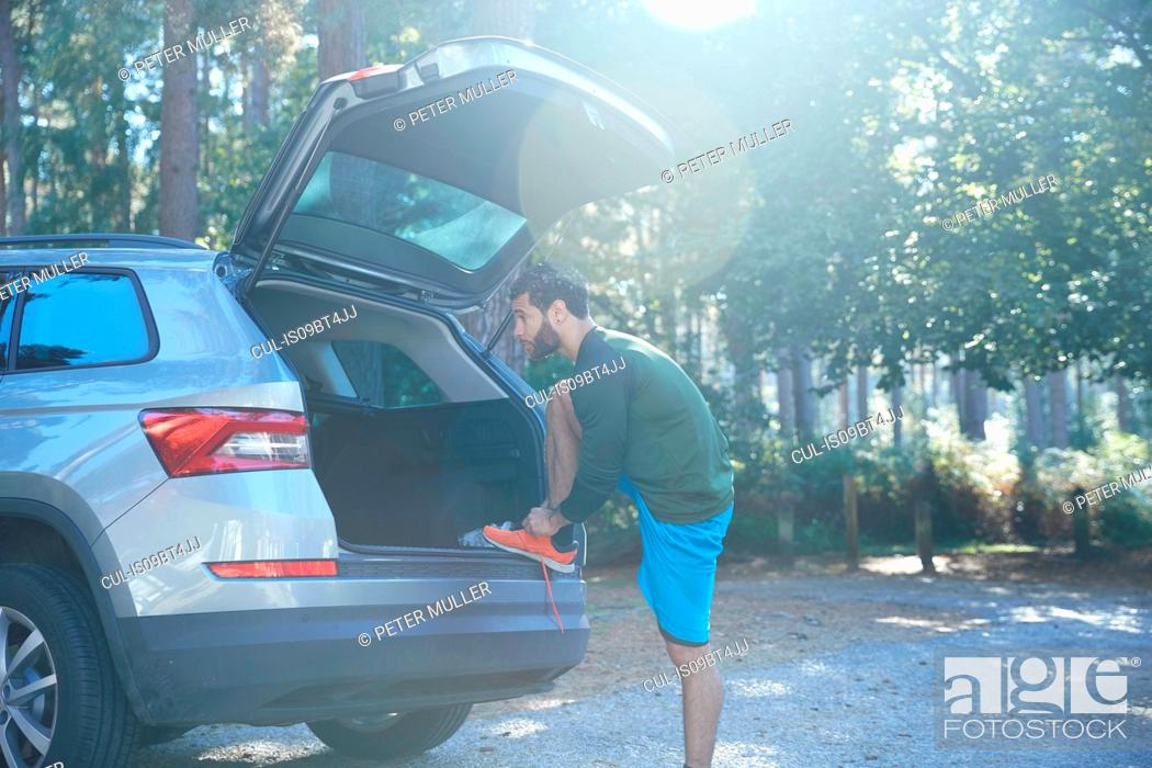 Stock Photo: Male runner tying laces on car boot in sunlit forest.