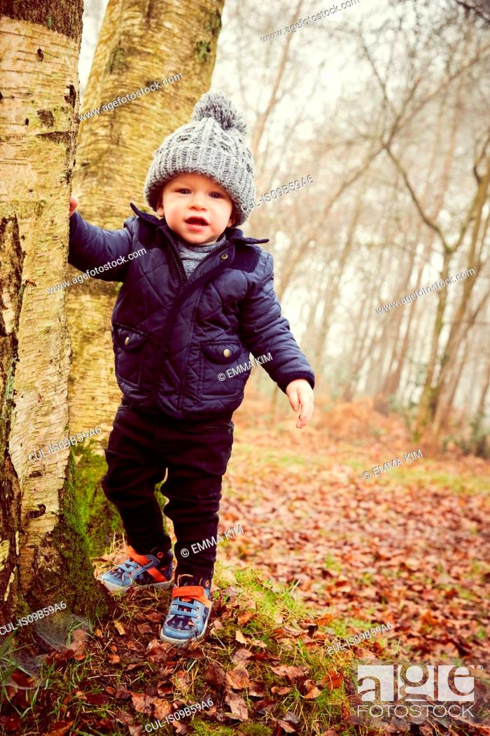 Stock Photo: Portrait of male toddler in knitted hat leaning against forest tree.