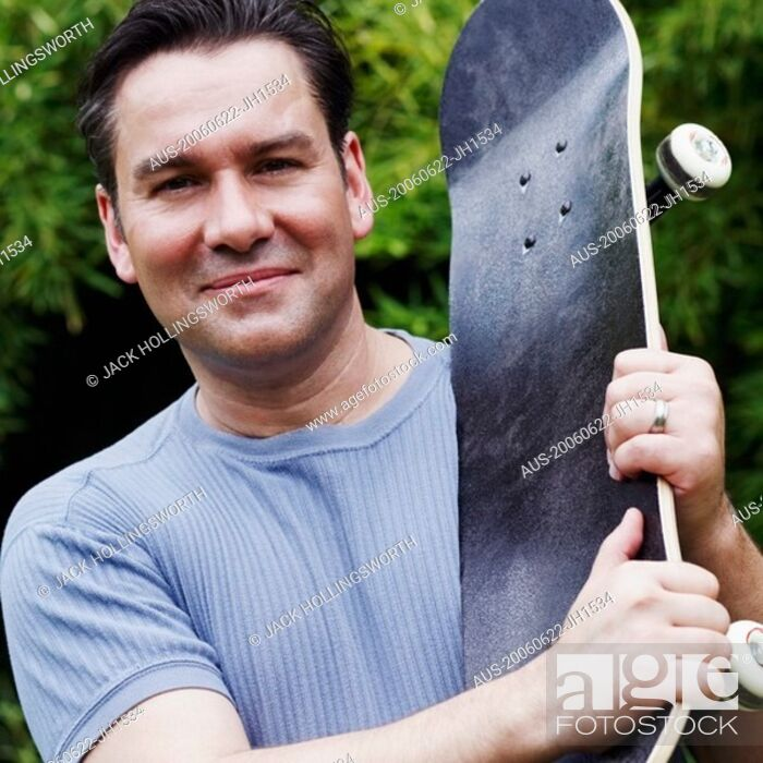 Stock Photo: Portrait of a mature man holding a skateboard.
