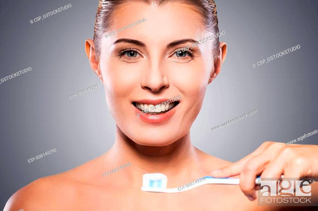 Stock Photo: Teeth care. Beautiful mature woman holding toothbrush near her mouth and smiling at camera while standing against grey background.