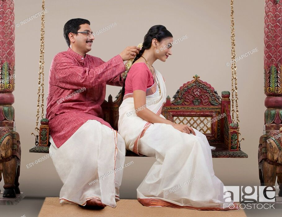 Imagen: South Indian man tying a Gajra on his wife's hair.
