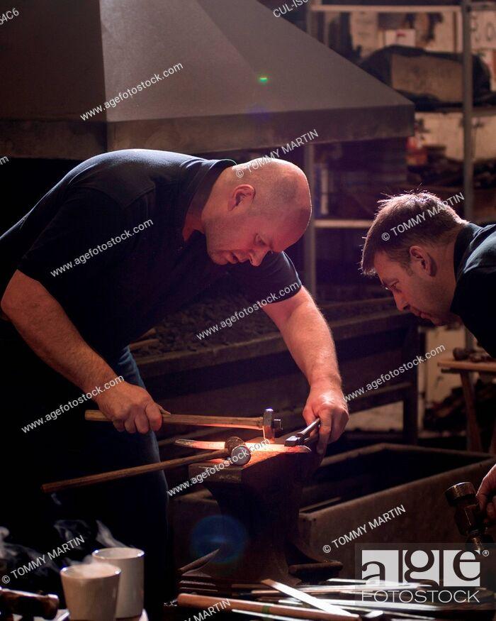 Stock Photo: Farriers forging horseshoe on anvil.