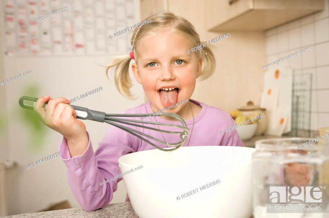 Stock Photo: Girl licking whisk covered with batter.